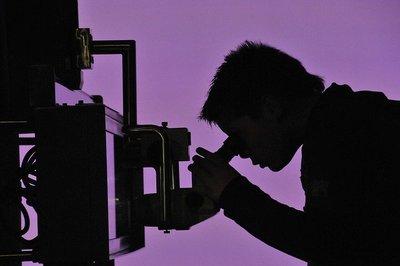 quelqu'un regarde dans un microscope