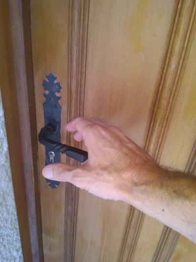 une main s'approche d'une poignée de porte