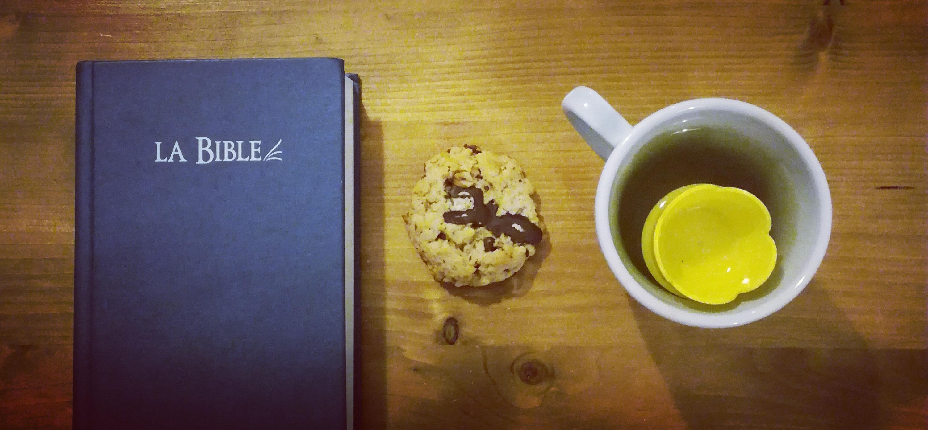 une Bible, un cookie et une tasse de thé